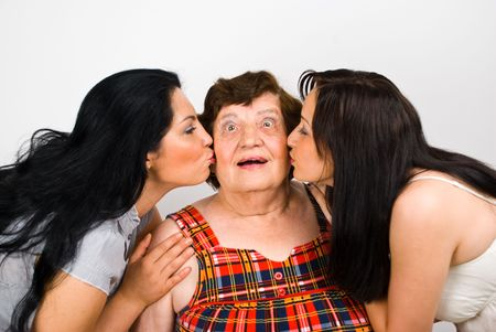 Surprised grandmother face being kissed by her two granddaughters  Stock Photo - 7209427