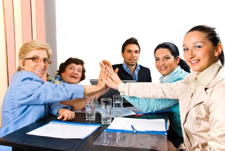 Group of business people giving high five and smiling  at  meeting or team spirit photo