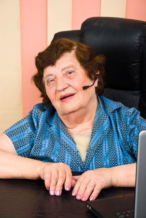 Portrait of smiling elderly woman customer service working in office photo