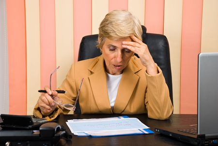 Elderly business woman having problems with graphics or a bad head ache looking down,she sitting  on chair at desktop photo