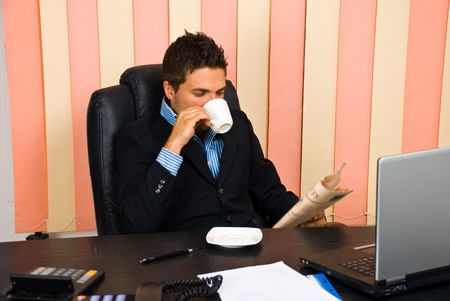 Manager reading news in his office and drinking a cup of coffee photo