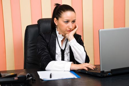 Bored business woman in office browsing internet on laptop photo