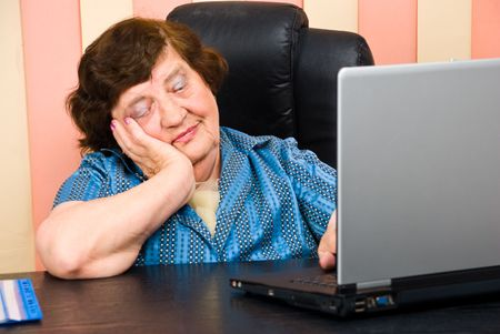 Bored elderly business woman using laptop in office photo