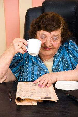 Elderly corporate woman sitting at desktop and reading the news in  the morning photo