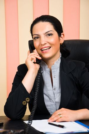 Portrait of beautiful happy business woman calling by telephone in her office photo