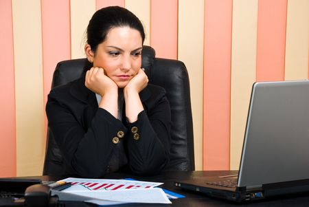 office wear: Sad business woman in office sitting with face resting in her hands and looking to laptop screen
