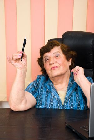 Elder business woman sitting in chair at office and holding a pencil in her hand Stock Photo - 7256720