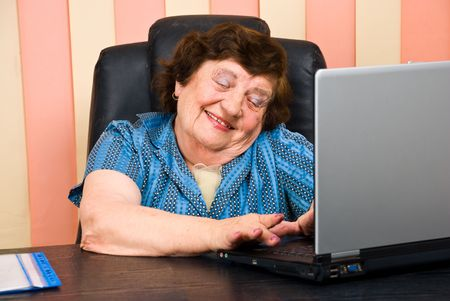 Elderly office woman having fun on laptop and laughing photo