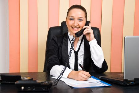 Young business woman talking by telephone and taking notes photo
