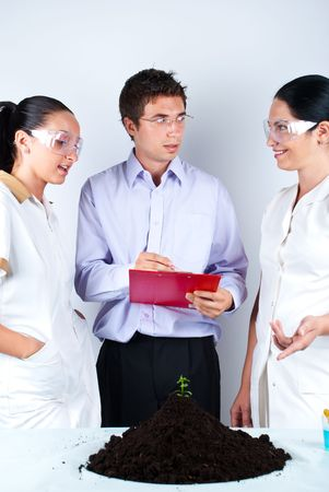 Three scientists  having a conversation about an experiment and the young man taking notes Stock Photo - 7310534