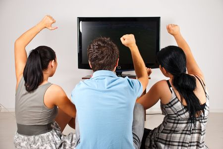 cheering fans: Rear view of three excited  soccer fans sitting on floor and  watching favorite team goal  at tv Stock Photo