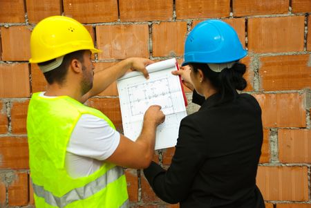 Back of two architects with blueprints working  on site,man pointing on project  photo