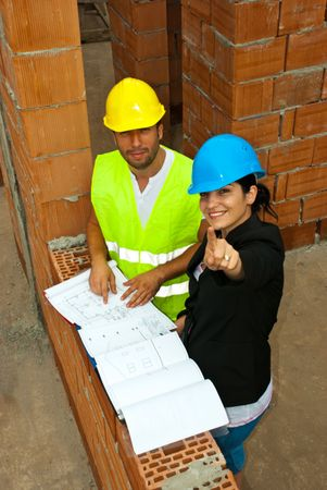 bricklayer: Two architects in a house under construction having a discussion and the woman pointing up to you