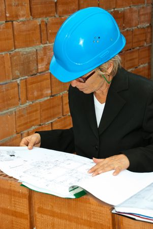 Senior architect woman with hard hat reading projects and  folders  in interior of a house under construction photo