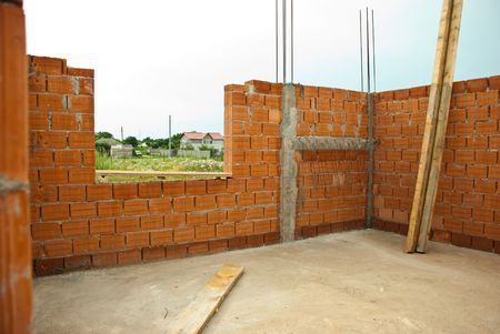 Interior of a house under construction with red brick walls   photo