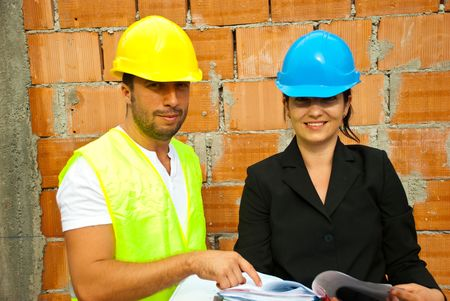 Two young smiling architects with plans  working on site and holding plans,man pointing to paper photo