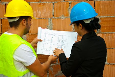 Back of two architects with helmet working in a house under construction and holding blueprints,selective focus on plan photo