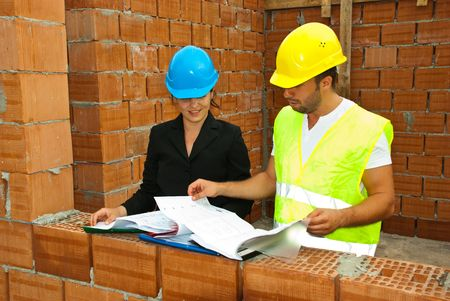 Constructions workers looking on  blueprints and folders in an unfinished house with  bricks wall photo