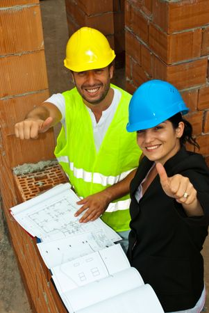 Top view of two happy architect team  on site giving thumbs up photo