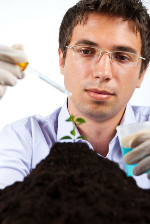 Researcher working in laboratory ,he holding a pipette and jar with blue chemicals photo