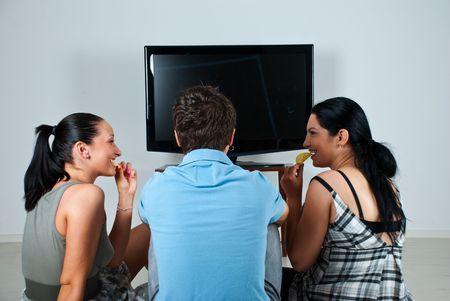 Tres amigos, tener una conversación divertida mientras viendo el partido de fútbol en tv y comer chips