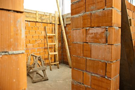 unfinished building: Detail of  a room with brick wall and wooden ladder in a house under construction