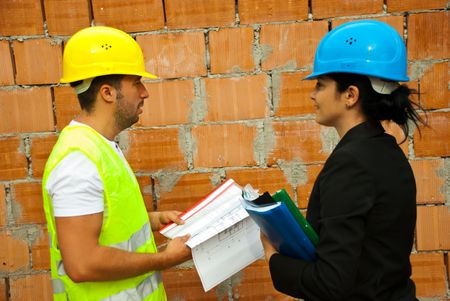 Two architects holding projects and  folders standing in profile and having a conversation on site photo