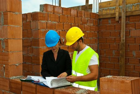 unfinished building: Two architects having a discussion and reading folders or looking on projects in a house under construction outdoor Stock Photo