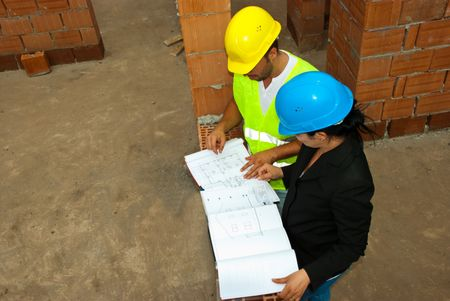 Top view of two construction workers people looking on projects in a house under construct photo