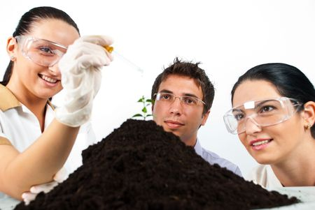 Happy biologists in laboratory making an experiment on a plant in soil photo
