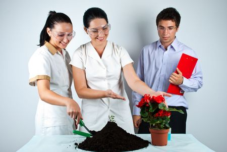 Three biologists working in laboratory ,they smiling and one of women showing to a  plant in patchwork Stock Photo - 7471048