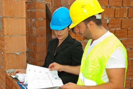Two young architects on site having a conversation and looking on projects photo