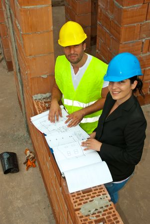 Top view of architects with plans on site looking up and smiling photo