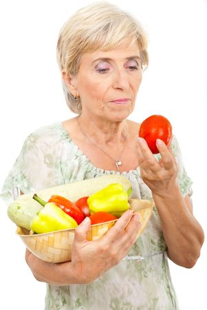 checking ingredients: Attractive aged woman holding fresh vegetables in a basket and looking at a tomato isolated on white background