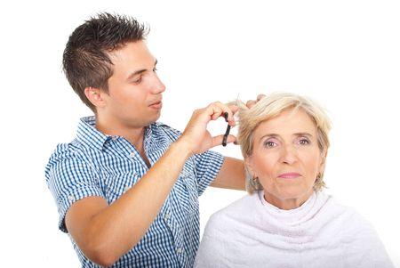 estilista: Estilista corta el pelo de un cliente de mujer senior en Sal�n de belleza aislado sobre fondo blanco  Foto de archivo