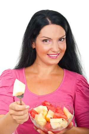 Young smiling woman holding a bowl with fresh melons salad and giving a piece of melon to you isolated on white background Stock Photo - 7564765