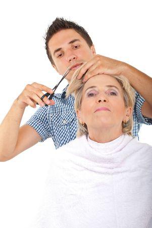 Hairdresser cut senior woman hair over white background photo