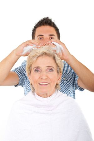 Hairdresser applying hair mousse on senior woman hair in a beauty salon photo