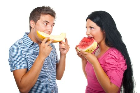 Young couple eating melons and looking each other smiling isolated on white background Stock Photo - 7590082