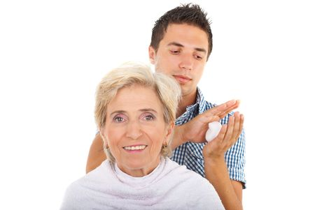 Hairstylist preparing to apply  hair mousse to a senior woman who smiling isolated on white background Stock Photo - 7590074