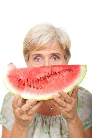 Senior woman holding a slice of watermelon next to her face isolated on white background photo