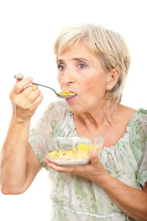 Senior woman standing in semi profile and eating cornflakes cereals isolated on white background photo