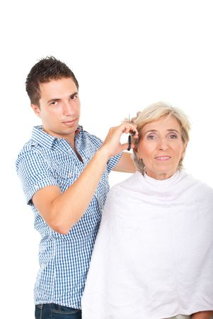 Hairdresser cutting senior woman hair and both smiling isolated on white background photo