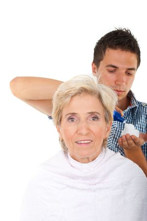 Hairstylist applying hair mouse to a smiling senior woman isolated on white background Stock Photo - 7590093