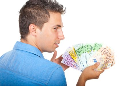 Young businessman standing in semi profile and looking over shoulder with handful of money isolated on white background,selective focus on money photo