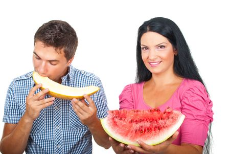 Healthy couple eating melons and smiling for you isolated on white background photo