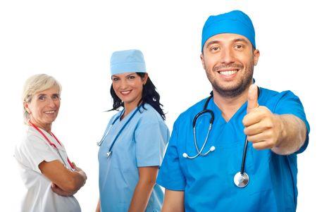 grupo de doctores: Exitoso equipo de doctores dando pulgares y mirando satisfechos de c�mara aislado sobre fondo blanco