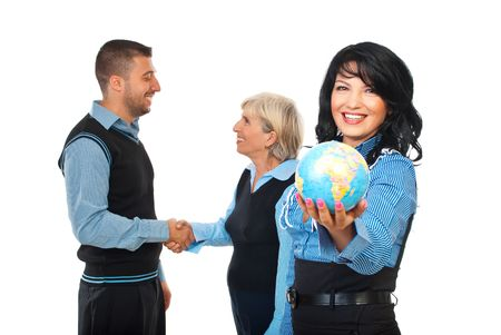 Happy business woman holding a world globe while two other business people shaking hands in background concept of international business relationship isolated on white background photo