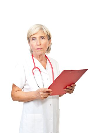Serious senior doctor woman  holding a clipboard and looking to you isolated on white background photo