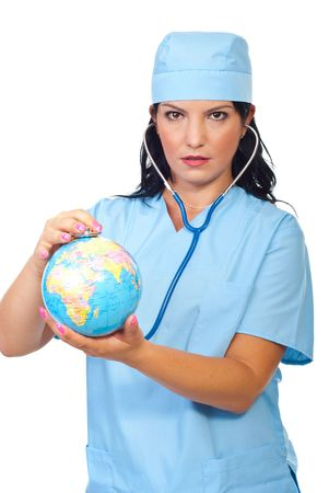 Serious doctor woman examine world globe with her stethoscope isolated on white background photo